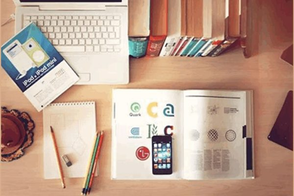 desk with laptop, books and stationery